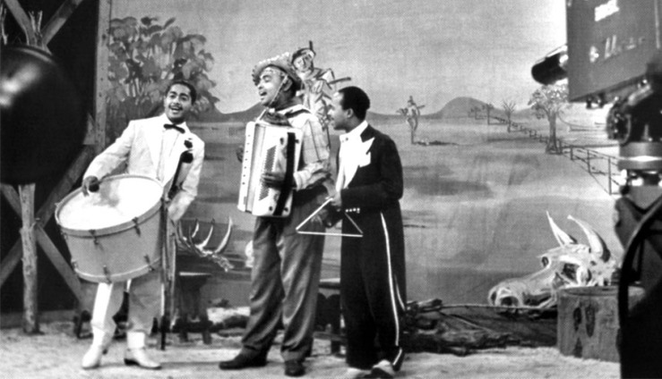 Luiz Gonzaga (center) recording in a traditional forró ensemble - zabumba (L), sanfona (accordion), and triangle.