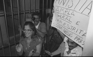 "Political prisoner Inês Etienne Romeo is freed immediately through the amnesty law on 29 August 1979. The sign reads: ""Amnesty: Broad; For everyone; unlimited. Free our prisoners."""