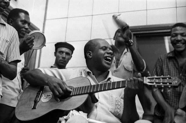 Candeia on the guitar in 1969, with Martinho da Vila behind him.